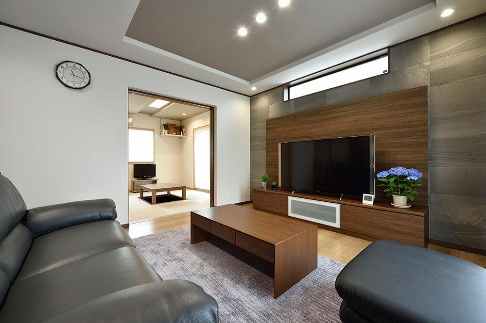 TVボード背面のエコカラットは砂岩の流れがモチーフ。室内に高級感が漂います。