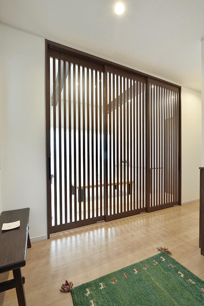 玄関とフリールームを隔てる扉はガラスの格子戸で、 開放感と目隠しを両立。