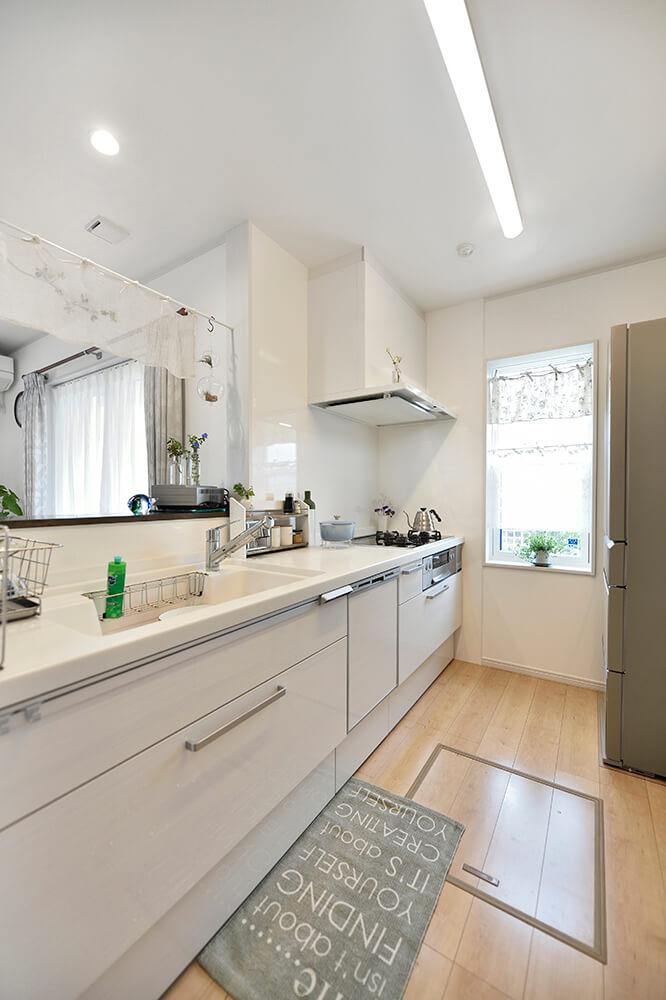 木目調のホワイトで統一されたキッチン。 窓辺のコーヒーカーテンはI様のお手製。