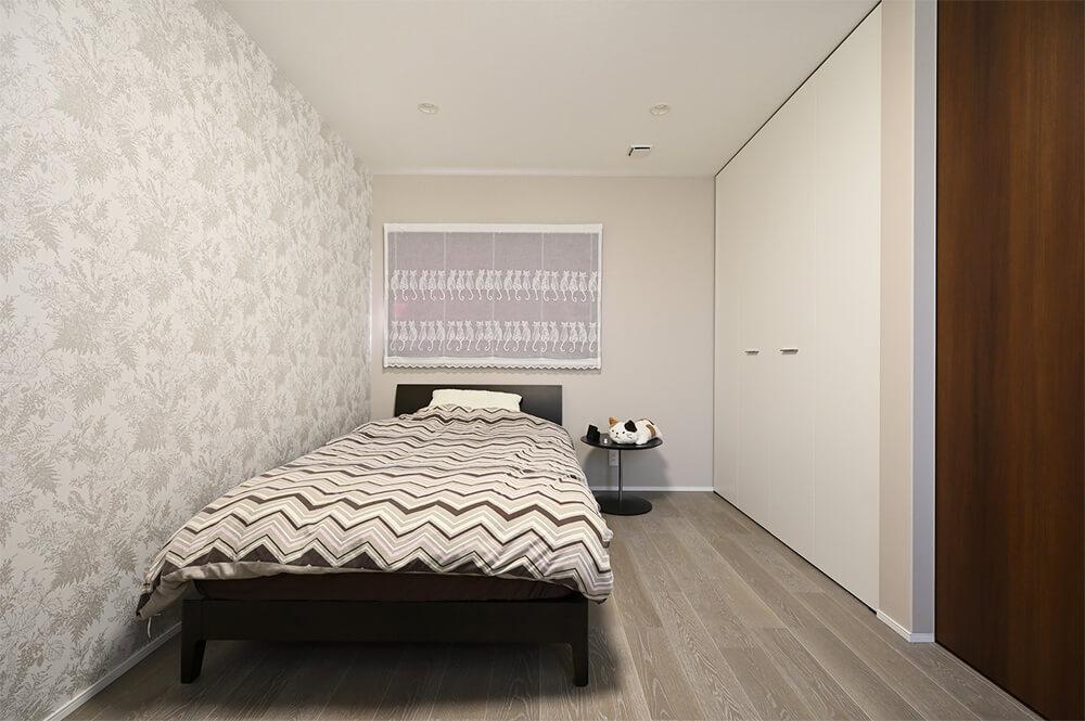 柔らかなグレーの床材を採用した奥様の寝室。猫の刺繍が入ったレースのカーテンがお気に入り。